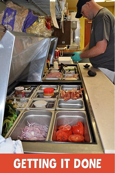 """Photo of a sandwich cooler with fresh ingredients and the text """"getting it done"""""""